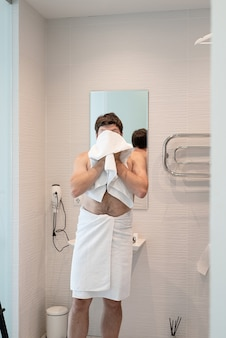 Health care. young adult man washing his face in bathroom, using towel