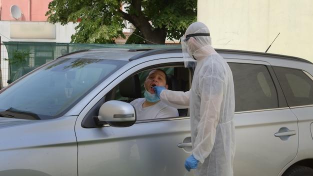Health caretaker taking saliva swab from man through automobile window.