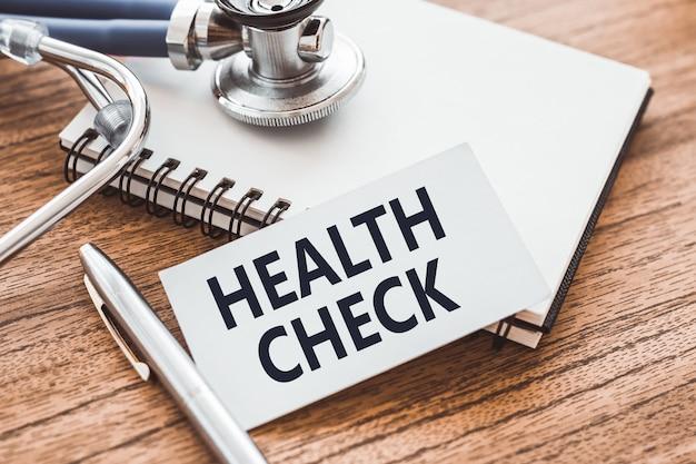 건강 검사-청진 기 및 의료 기록 카드 나무 테이블에 명함에 텍스트.