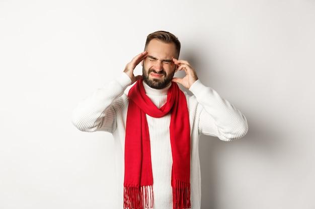 건강 개념입니다. 두통이 심하고 머리를 만지고 편두통으로 찡그린 남자, 겨울 스웨터와 빨간 스카프, 흰색 배경에 서 있는 남자