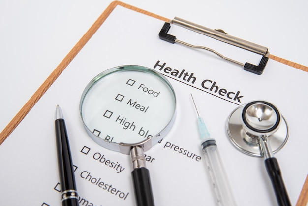 Health concept with clipboard and health check related items.