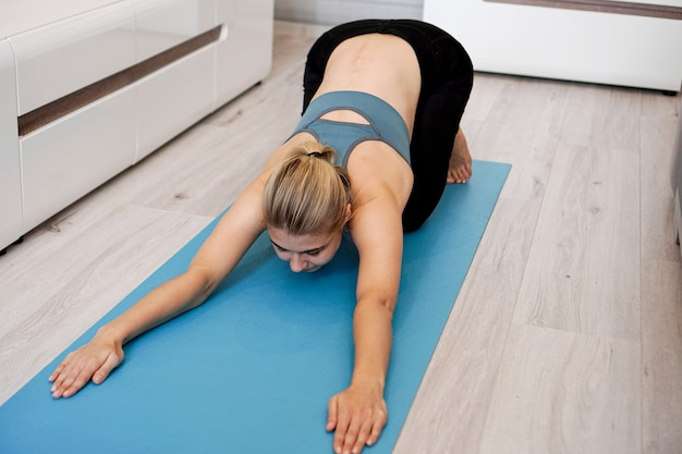 Health concept. woman meditating or doing yoga exercise at home
