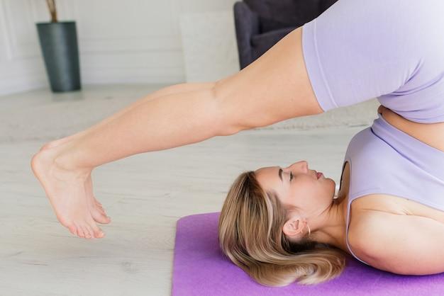 Концепция здоровья. молодая красивая женщина делает упражнения йоги в современной комнате