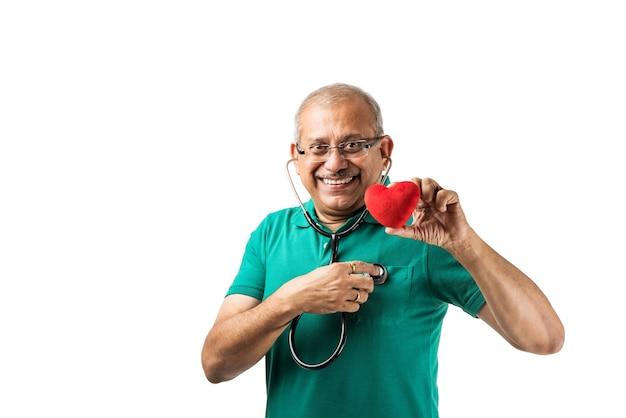 健康志向のインドのアジアのシニア男性の成人が聴診器で心臓の鼓動をチェックし、おもちゃの心臓やリンゴを手に持って、okの兆候を示しています