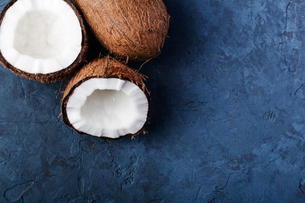 Содержание здоровья, композиция на темно-синем столе из камня, половинки кокоса, весь кокос, вид сверху