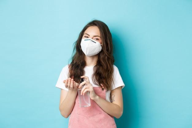 건강, 코로나바이러스, 사회적 거리 개념. 방독면을 쓴 젊은 여성은 손 소독제를 사용하여 세균에서 손을 깨끗이 하고 손바닥, 파란색 배경에 방부제를 바릅니다.