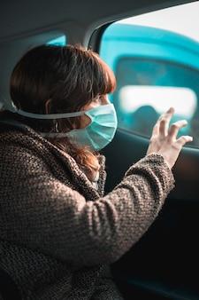 健康covid-19危機、車の窓の外を見て若い白人悲しいブルネット