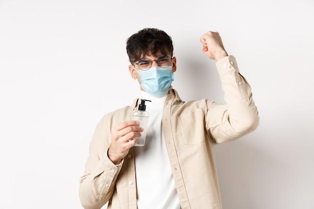 健康、covidおよび検疫の概念。コロナウイルスと戦う意欲のある幸せな青年は、白い壁に立って、手の消毒剤を見せ、勝利を収めて手を上げました。