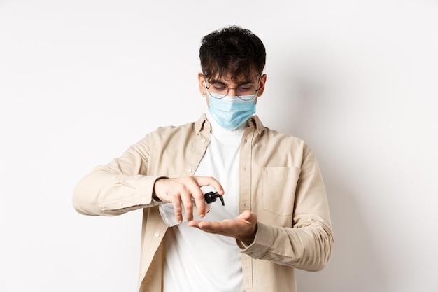 健康、covidおよび検疫の概念。眼鏡と手指消毒剤を使用したフェイスマスクの若いヒスパニック系の男は、白い壁に立って、消毒剤を適用します。