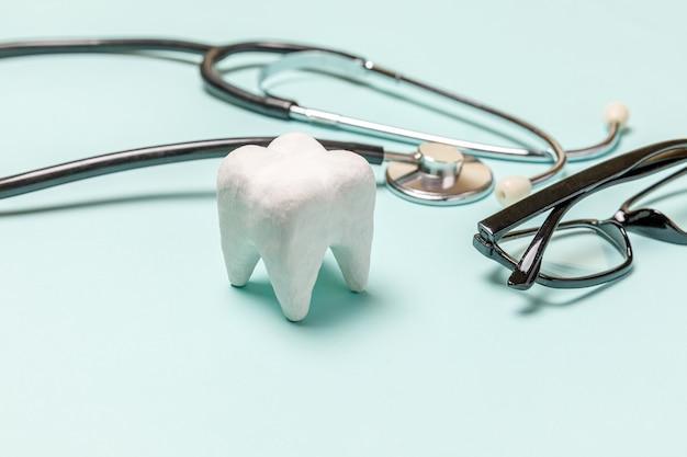 건강 치과 치료 개념입니다. 파스텔 파란색 배경에 격리된 의학 장비 청진기 흰색 건강한 치아 안경. 치과 의사를 위한 기구 장치. 치과 구강 위생, 치과 의사의 날.