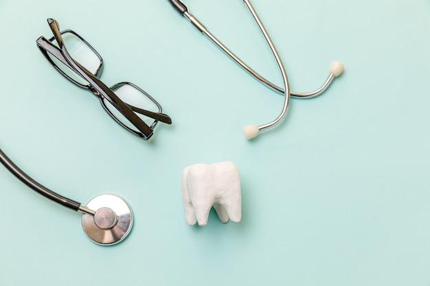 健康歯科医療の概念。パステルブルーの背景に分離された医療機器聴診器白い健康な歯のメガネ。歯科医のための器具装置。歯科口腔衛生、歯科医の日。