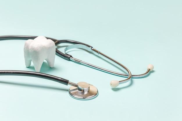 健康歯科医療の概念。パステルブルーの背景に分離された医療機器聴診器白い健康な歯。歯科医のための器具装置。歯科口腔衛生、歯科医の日。
