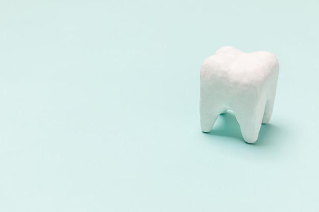 건강 치과 치료 개념입니다. 파스텔 블루 배경에 고립 된 흰색 건강한 치아 모델