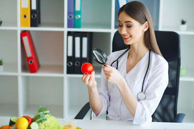 Health. the doctor signs out a diet plan. the dietitian holds in the handfuls of fresh tomato. fruits and vegetables. young doctor with a beautiful smile at the office.