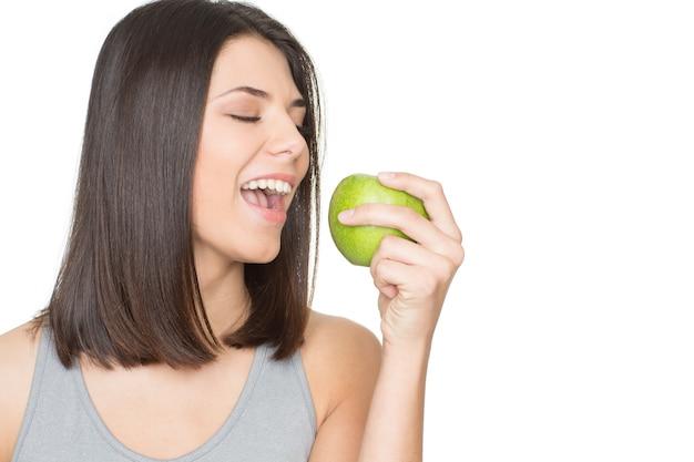 健康は素晴らしい気分です。側面の白いコピースペースで隔離の彼女の手に青リンゴを持つゴージャスな幸せで健康な若い女性