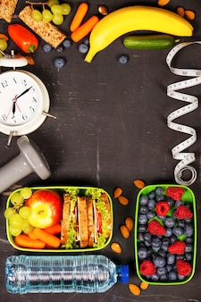 Health & fitness food in lunch boxes, measuring tape  and alarm
