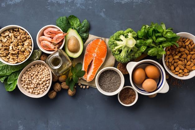健康食品のフィットネス。暗い背景の上面にオメガ3の食料源。野菜、魚介類、ナッツ、種子などの脂肪酸を多く含む食品