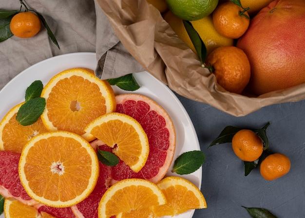 Здоровая пища из цитрусовых с апельсинами и грейпфрутом на сером фоне гранж в круглой тарелке. богат антиоксидантами, витаминами. вид сверху. закрыть вверх