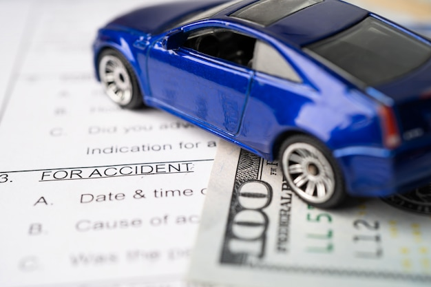 Health insurance accident claim form with us dollar banknotes money and car.