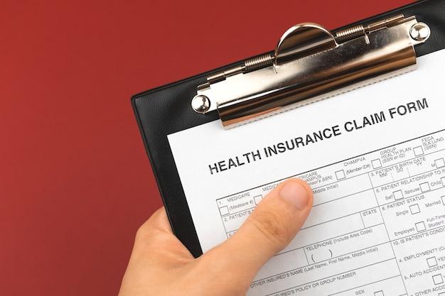 손과 클립보드에 있는 건강 보험 계약. 레드 부르고뉴 배경입니다. 의료 및 비즈니스 문서 사진