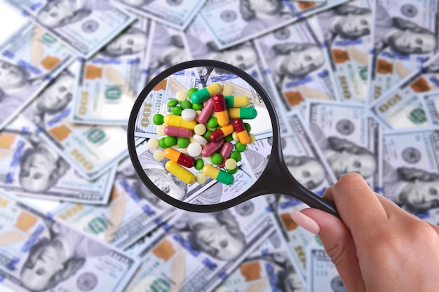 Health insurance. assortment pills in magnifier against  of many dollar banknotes