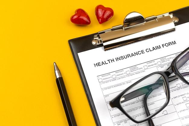 건강보험 청구서 양식입니다. 노란색 바탕 화면에 클립보드, 펜 및 빨간색 하트가 있는 비즈니스 바탕 화면. 상위 뷰 사진