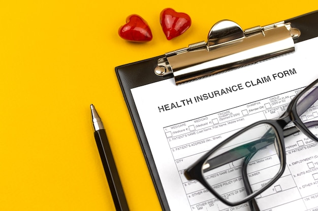 Health insurance claim form. business desktop with clipboard, pen and red hearts on a yellow desktop. top view photo