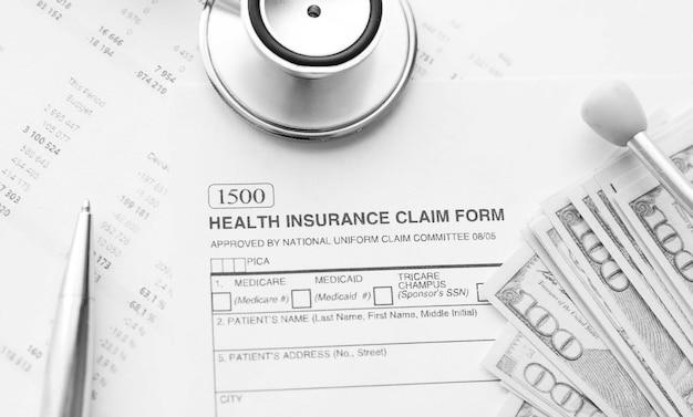 건강 보험 청구 양식. 청진 기 및 달러 지폐와 개별 의료 건강 보험 정책.