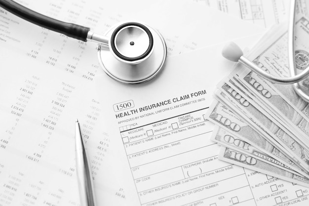 Health insurance claim form. individual medical health insurance policy with stethoscope and dollar banknotes.