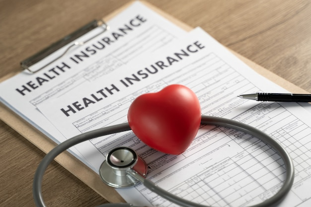 Health insurance in clipboard, stethoscope and heart