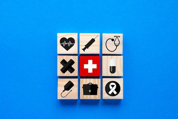Концепция медицинского страхования, синий фон с деревянными блоками, содержащими медицинские символы, копией пространства