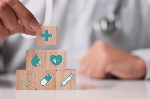 건강 보험 개념, 의료 아이콘이 있는 나무 큐브를 들고 있는 의사