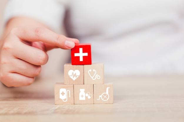 Health insurance concept,  hand arranging wood block stacking with icon healthcare medical