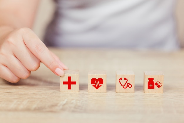 Health insurance concept, hand arranging wood block stacking with icon healthcare medical.