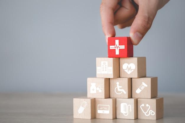 健康保険の概念、手アイコンヘルスケア医療と積み重ねウッドブロックを配置します。