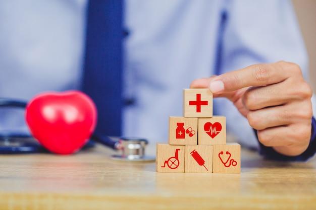 건강 보험 개념, 아이콘 건강 의료와 나무 블록 스태킹을 배열하는 손.