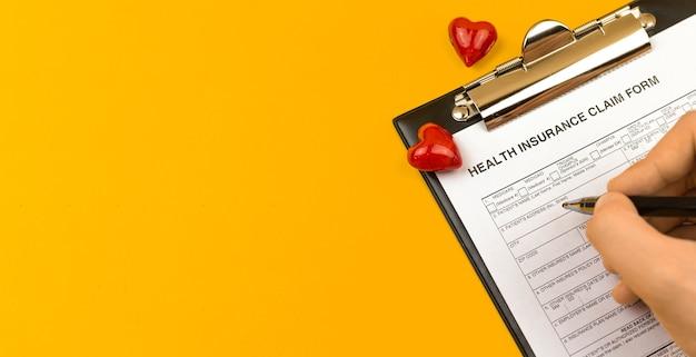건강 보험 양식입니다. 노란색 바탕 화면에 클립보드, 펜 및 빨간색 하트가 있는 비즈니스 바탕 화면. 상위 뷰 및 복사 공간 사진