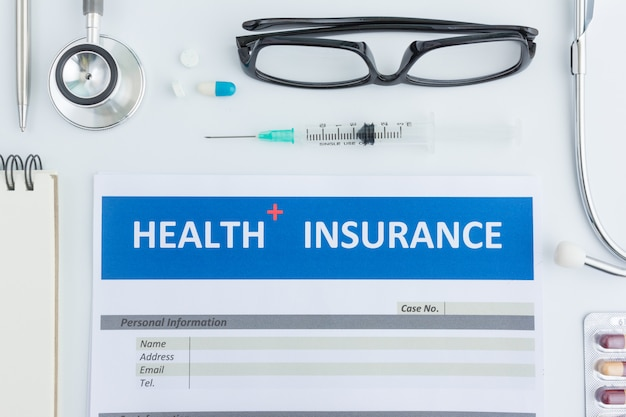 Health insurance form with stethoscope in top view