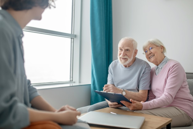 Медицинская страховка. старшая пара разговаривает с агентом страховой компании и выглядит вовлеченной
