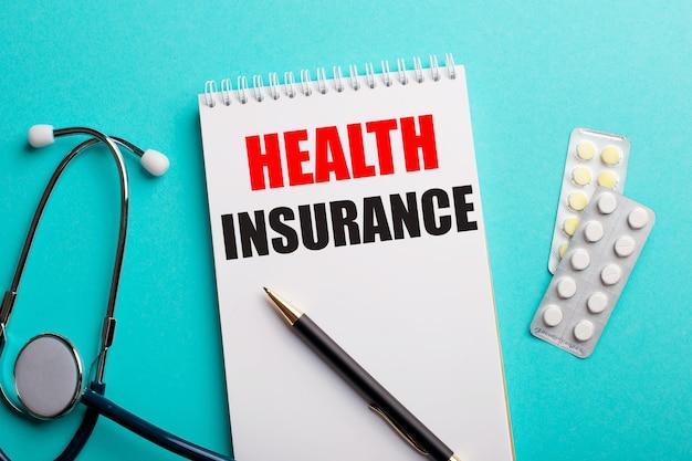 Страхование здоровья написано в белом блокноте на синем фоне возле стетоскопа и таблеток. страховая концепция.