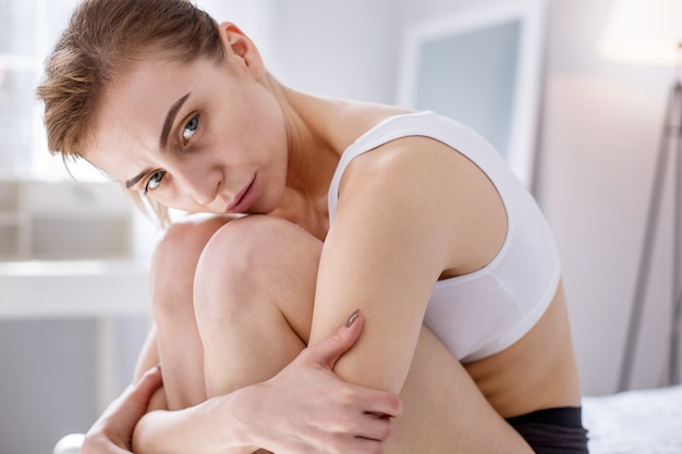 健康問題。ベッドに座っている間あなたを見ている深刻な病気の女性の上面図