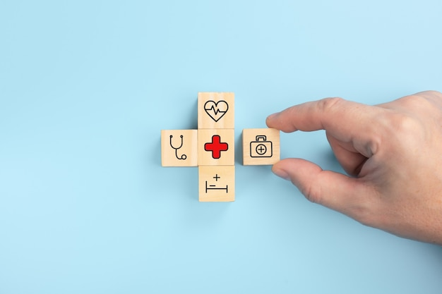 Health medical insurance concept, hand hold wooden block with icon healthcare medical.