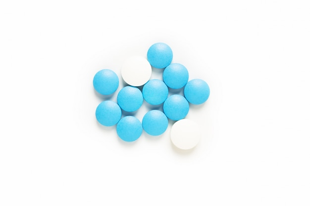 Health and medication concept blue and white pills drug or tablets on white with copy space
