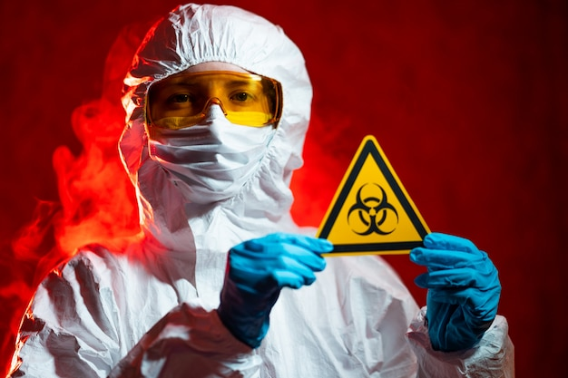 Health, medicine and pandemic concept - female doctor holding boihazard caution sign