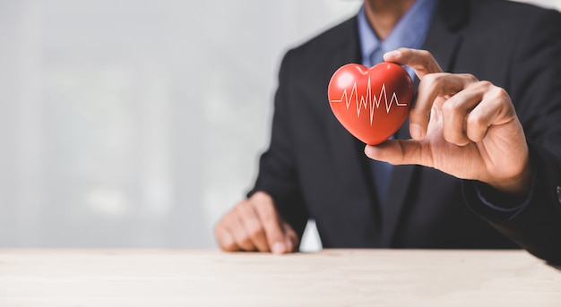 Health, medicine, people and cardiology concept - close up of happy man with cardiogram on small red heart