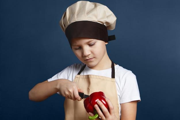 健康、栄養、食品。空白の壁に立って、新鮮な野菜と一緒に健康的な夕食や昼食を調理しながらナイフで赤唐辛子をはがしているシェフの帽子をかぶった真面目な集中少年の写真