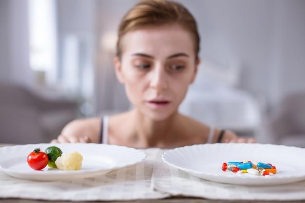 健康または死。元気のない病気の女性の前に立っている2つのプレートの選択的な焦点