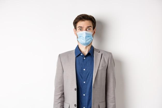 健康、パンデミック、ビジネスコンセプト。スーツと医療マスクの眉を上げる驚きの男、カメラ、白い背景にショックを受けた凝視。