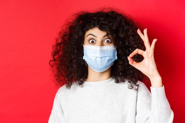 健康、パンデミック、そしてcovidのコンセプト。興奮した女性は、医療用マスクを着用し、承認を得て、赤い壁に立って、はい、大丈夫な兆候を示しています。