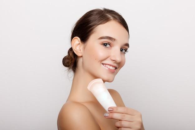 健康、人、美容のコンセプト-頬に化粧クリームを塗った若い女性の美顔。スキンケアのコンセプト。白で隔離のクローズアップの肖像画。清潔で新鮮な肌を持つ若い成人女性の顔。